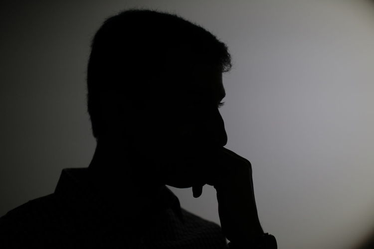 Close-up of silhouette man against white background