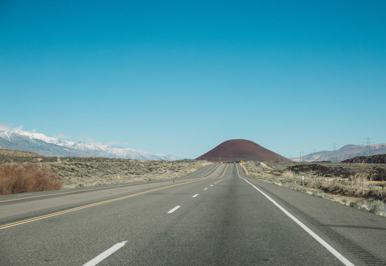 Empty Road Leading Towards Mountains Against Clear Blue Sky