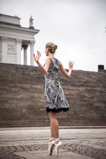 Full length of female ballet dancer dancing against staircase in city