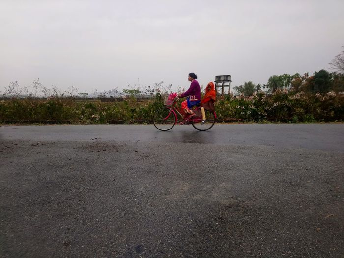 Woman with friend riding bicycle on road against sky