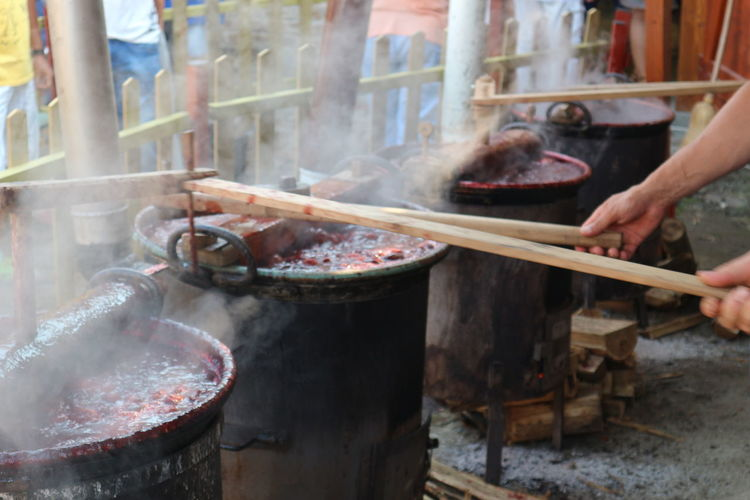 Cooking plum jam in big pots