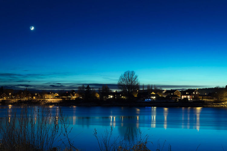 Architecture Beauty In Nature Blue Building Exterior City Dusk Illuminated Lake Nature Night No People Outdoors Plant Reflection Scenics - Nature Sky Tranquil Scene Tranquility Tree Water