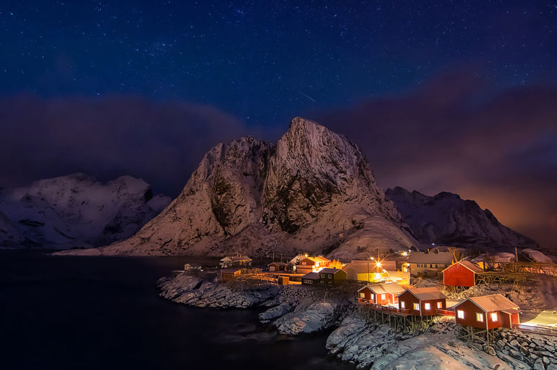 Illuminated building by mountains against sky at night