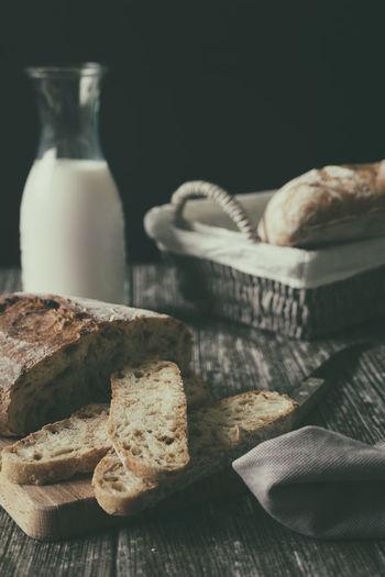 Sliced homemade artisan bread ciabatta on wooden table food blog recipe copy space breakfast idea
