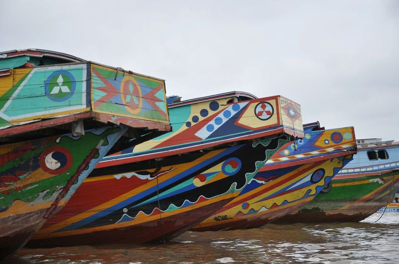 Multi colored boats moored on beach against sky