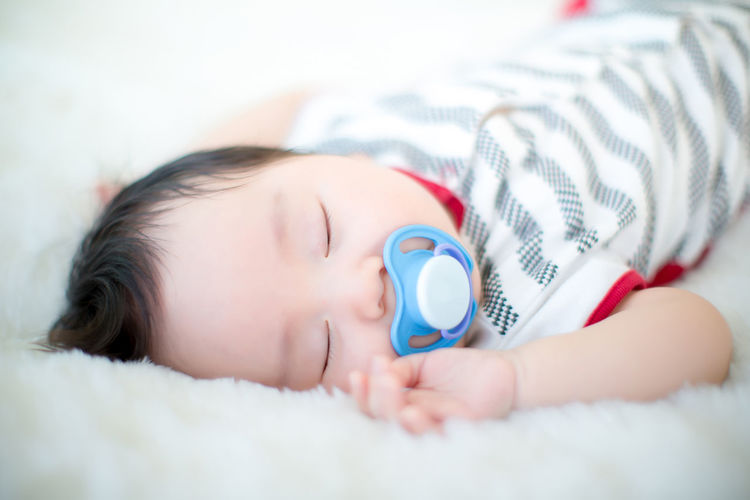 Close-up of cute baby boy with pacifier sleeping on bed