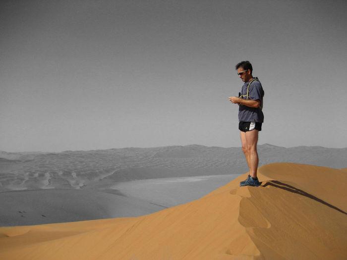 Man Standing On Sand Dune At Desert
