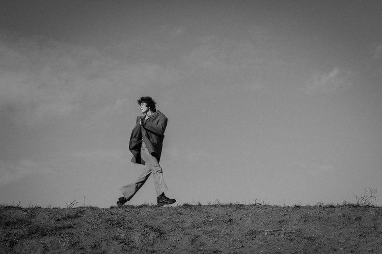 Full length of woman walking on land against sky