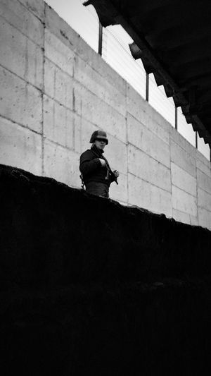 Solider with rifle standing against wall