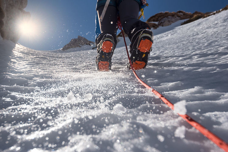 Low section of person skiing on snowcapped mountain