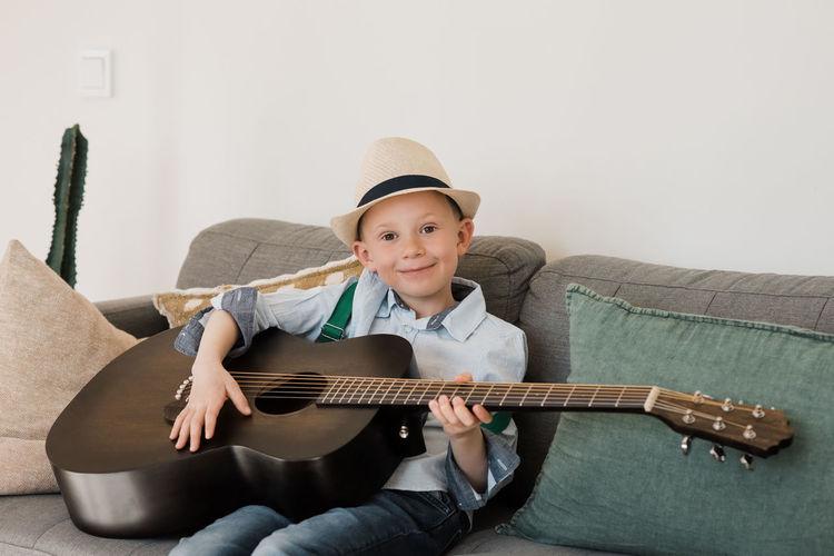 Portrait of a smiling boy sitting on sofa