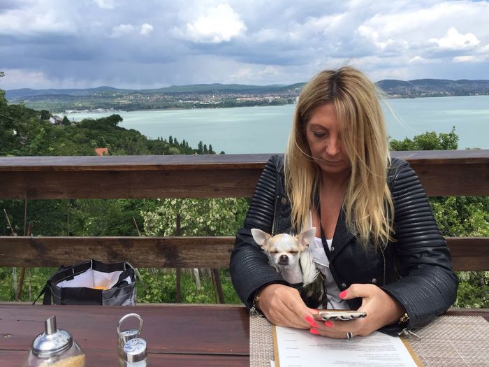 Woman with chihuahua using mobile phone against lake