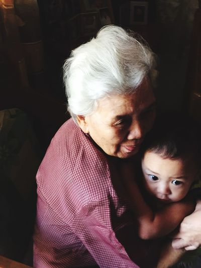 Happy grandmother embracing grandson at home
