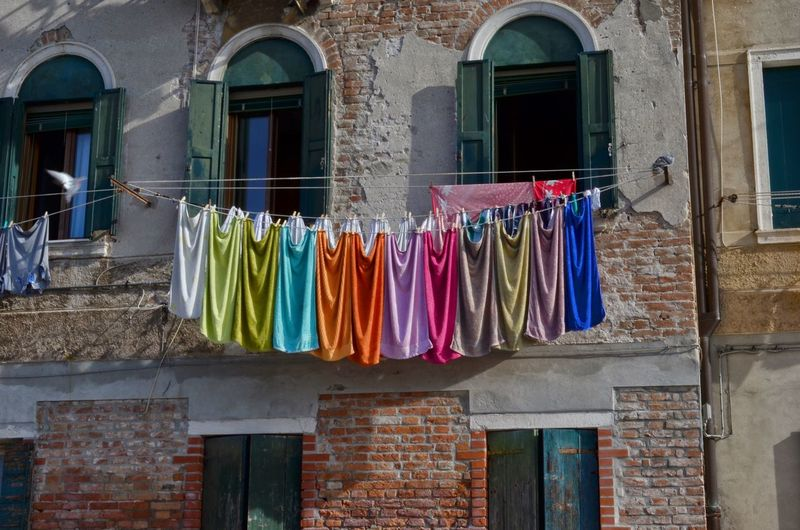 Multi colored clothes drying outside building