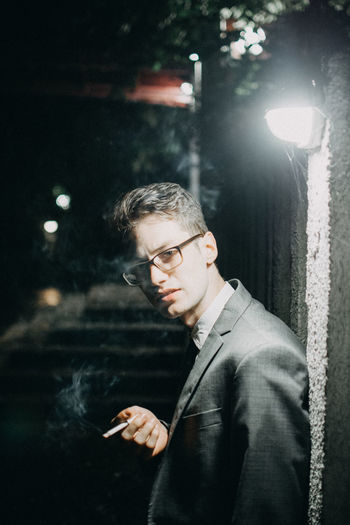 Young man smoking a cigarette Light Smoking Suit Architecture Casual Clothing Cigarette  Clothing Eyeglasses  Glasses Illuminated Lifestyles Looking Looking Away Night One Person Outdoors Portrait portrait of a friend Real People Standing Waist Up Young Adult Young Men