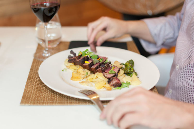 Midsection Of Person Eating Food Served On Table At Restaurant