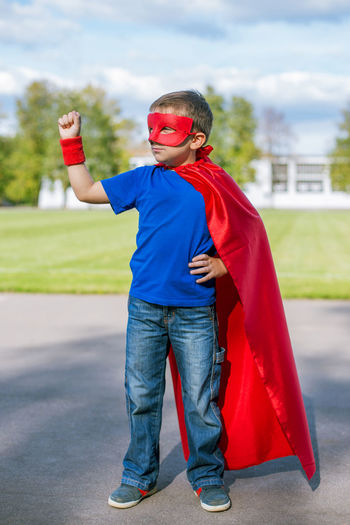 Full length of boy in superman costume standing on road against sky