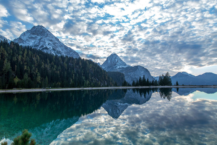 Idyllic shot of mountains against sky reflecting in lake