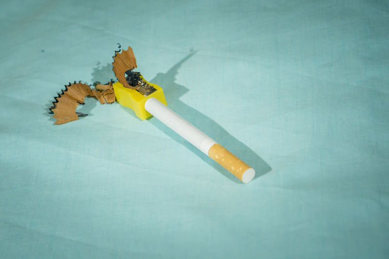 High angle view of cigarette on table against blue background