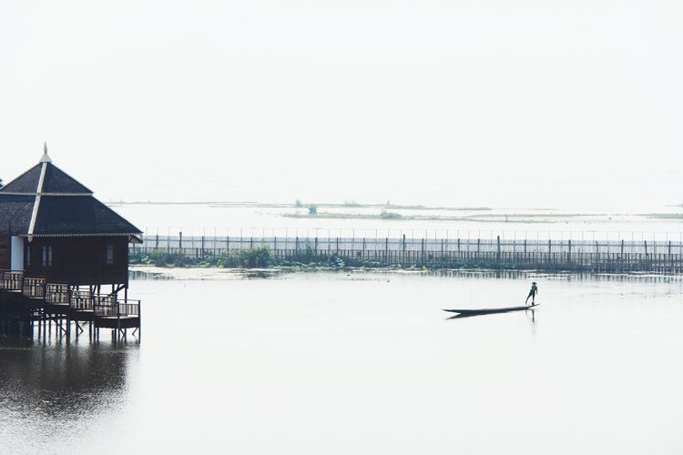 The Boat Man row by his leg Water Sea Sky Architecture Built Structure Building Exterior Horizon Over Water Stilt House Tranquil Scene Thatched Roof The Traveler - 2019 EyeEm Awards