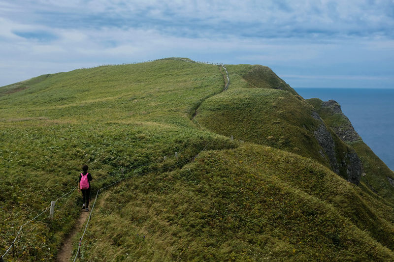 Rebun Island Hokkaido,Japan Leisure Activity Beauty In Nature Scenics - Nature One Person Mountain Green Color Hiking Activity Day Non-urban Scene Rear View Real People Nature Lifestyles Sea Sky Water Tranquil Scene Tranquility Full Length Outdoors Looking At View