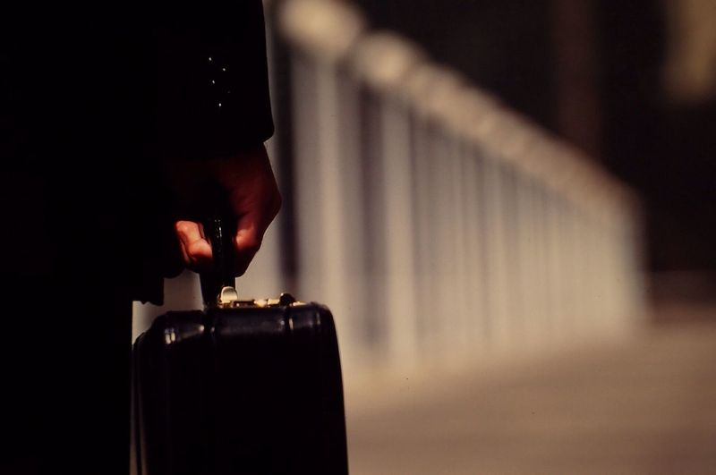 Midsection of person holding suitcase