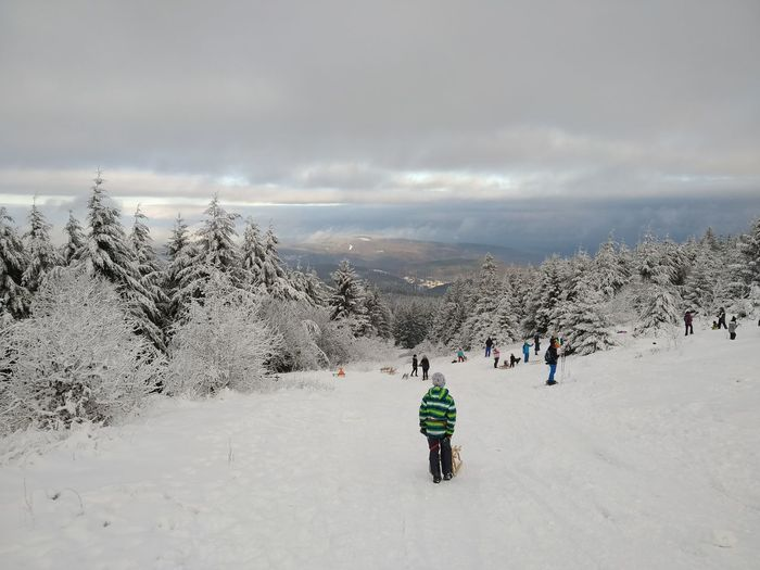 Rear view of people on snow covered mountain against sky