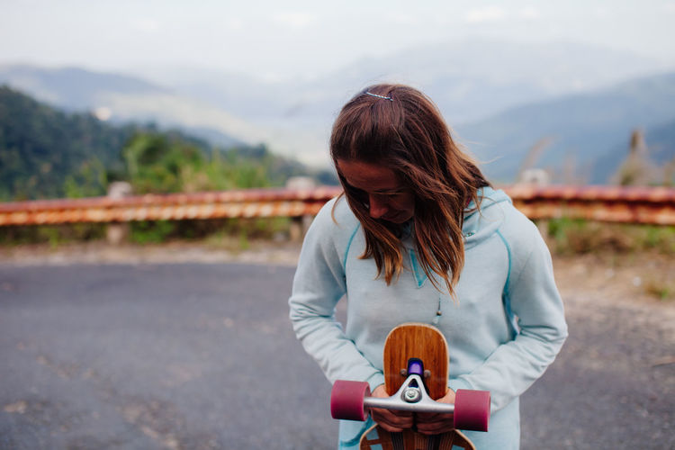 Woman with skateboard on road
