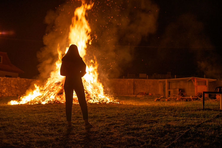 Rear view of young woman looking at bonfire