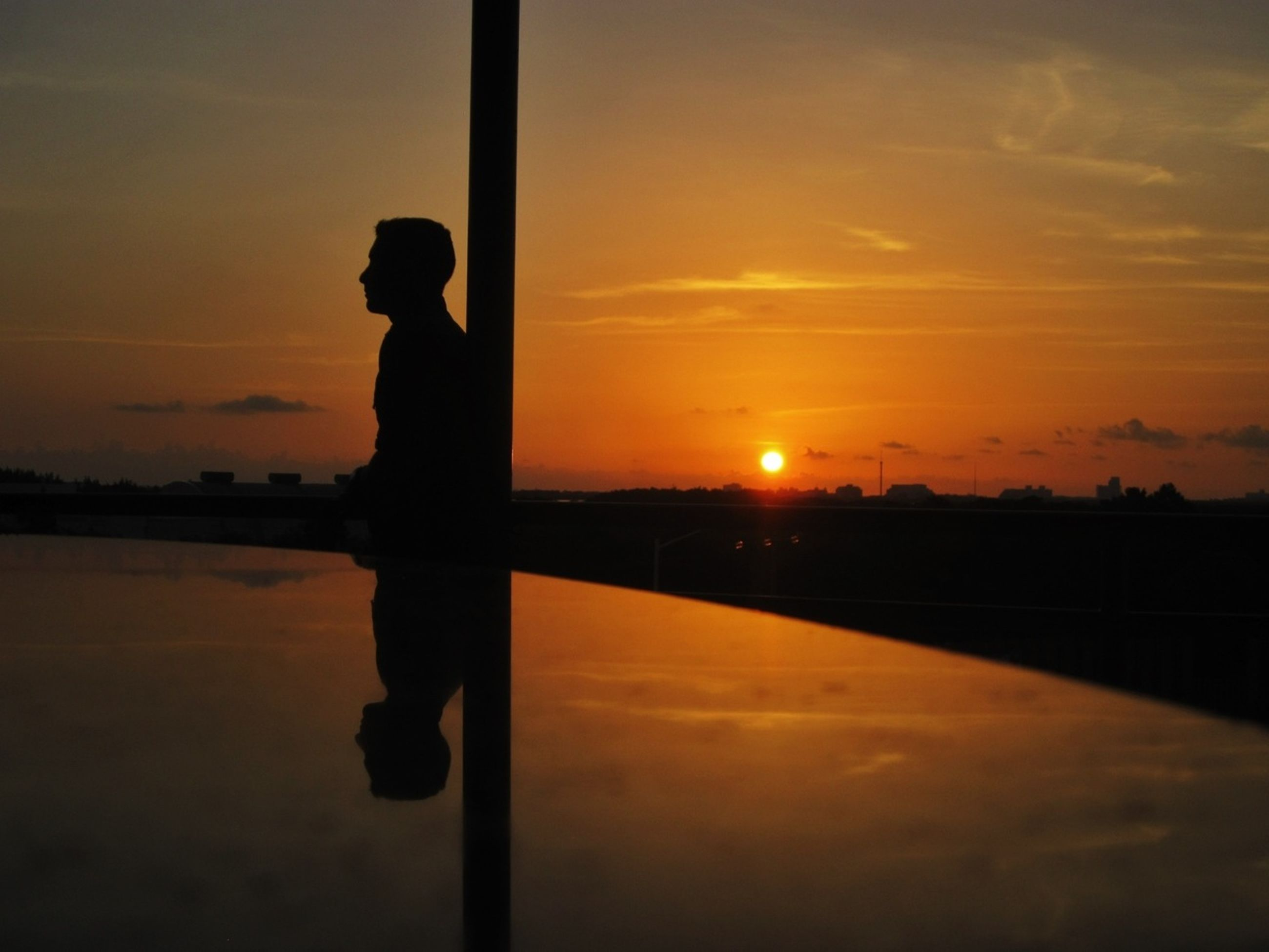 sunset, silhouette, orange color, sun, sky, standing, lifestyles, water, scenics, leisure activity, beauty in nature, tranquility, cloud - sky, nature, idyllic, tranquil scene, reflection, full length
