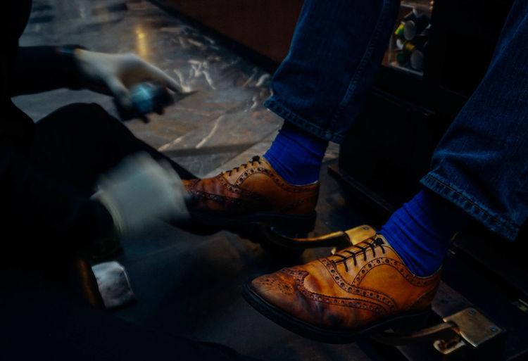 Blurred motion of shoeshiner polishing shoes of male customer