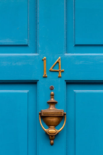 House number 14 on a blue wooden front door in london