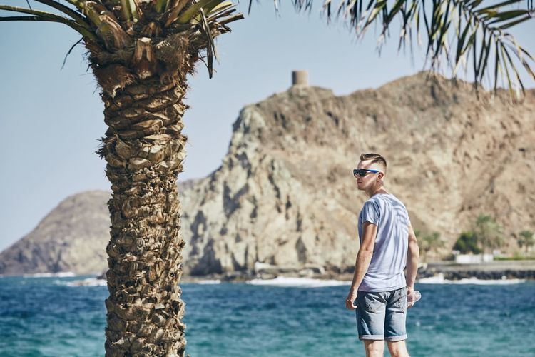 Man wearing sunglasses while standing at beach