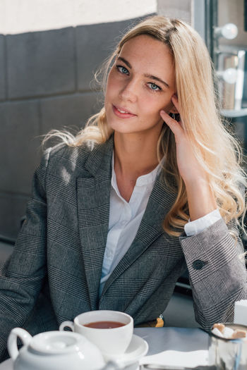 Elegant woman with beautiful eyes One Person Young Adult Young Women Hair Blond Hair Women Portrait Front View Coffee Cup Looking At Camera Food And Drink Beautiful Woman Hairstyle Sitting Table Drink Well Dressed Blue Eyes Adult Mug Coffee - Drink The Modern Professional