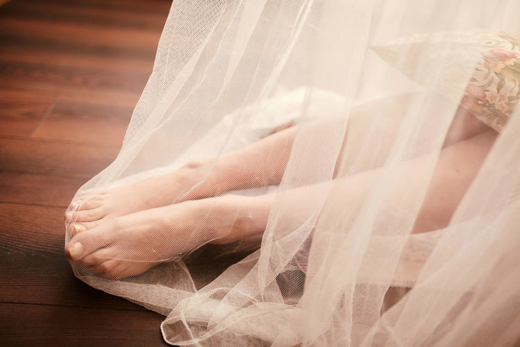 Low section of woman sitting under veil at hardwood floor