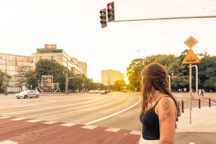 Young woman standing on city street against clear sky during sunset