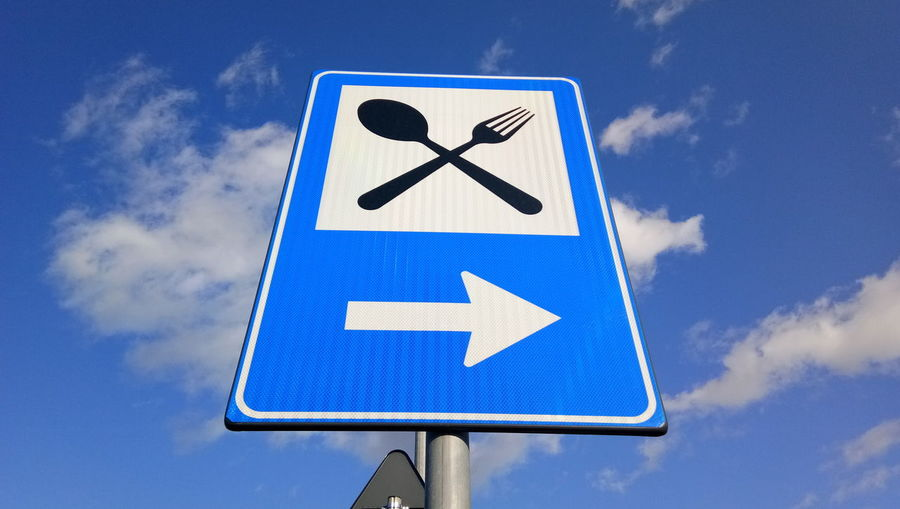 EyeEm Selects Road Sign Blue Information Medium Communication Guidance Direction Human Representation Arrow Symbol Sky Close-up
