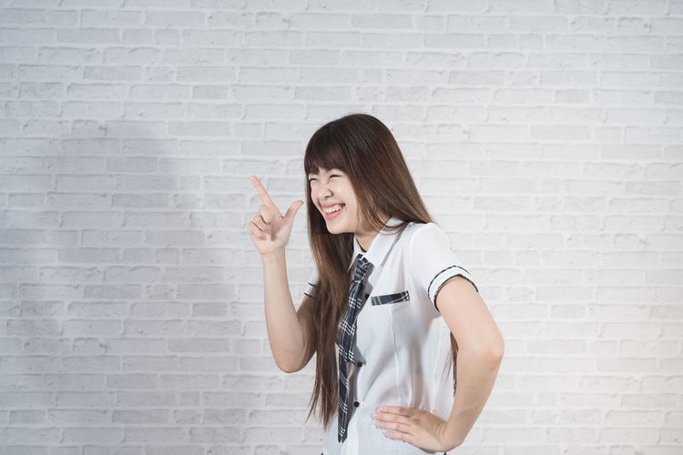 Happy young woman gesturing against wall