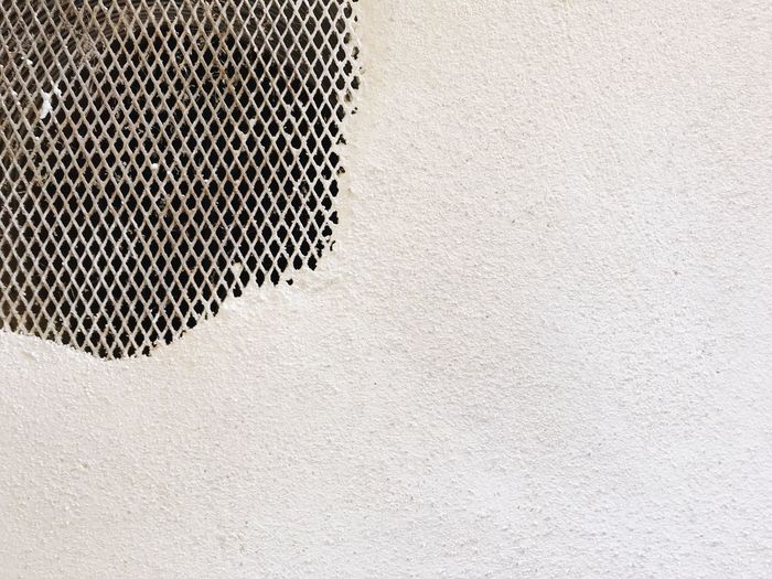 Close-up of metal grate in white textured wall