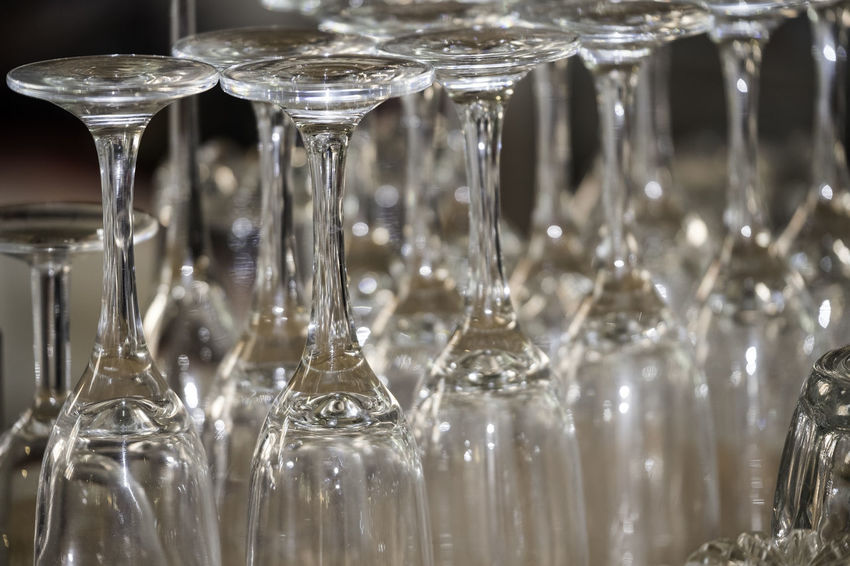 Drinking glasses in rows, upside down. Close-up with no people or brands visible. Drinking Glasses Glasses Reflection Wine Glasses Drinking Glass Drinking Receptacle Glass Indoors  No People