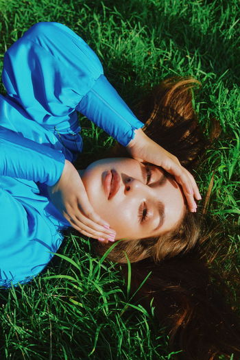 Portrait of woman lying on grass