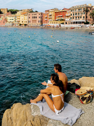 Friends sitting on seashore against buildings