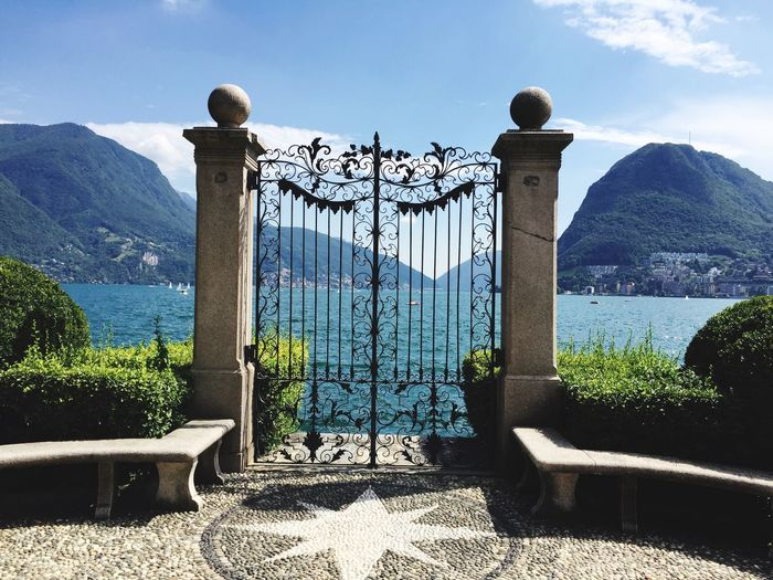 Manson Rich Sommer Green Park Lugano Switzerland Lugano Mauntain Lake Gate Plant Sky Nature Day No People Sunlight Gate Architecture Cloud - Sky Closed Tree Protection Water Built Structure Beauty In Nature Metal Outdoors