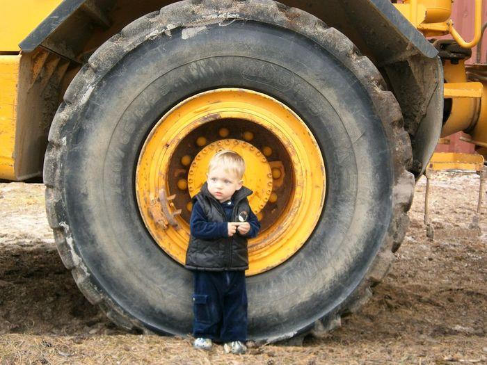 Boy Standing By Tire On Field