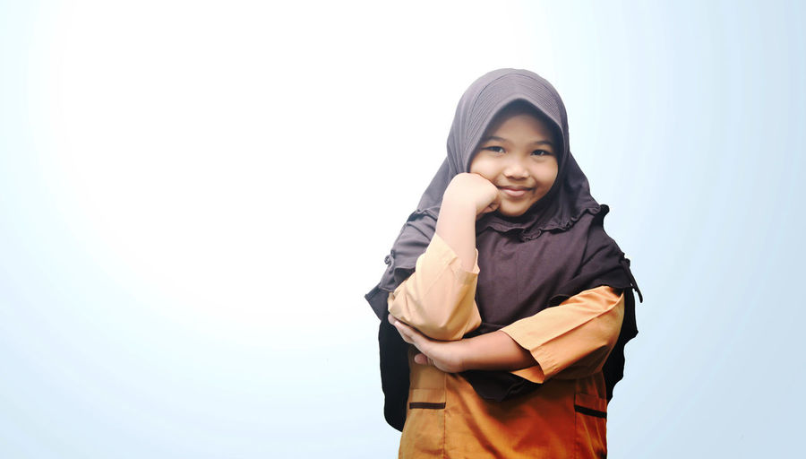 Portrait Of Happy Girl Wearing Hijab While Standing Against Clear Sky