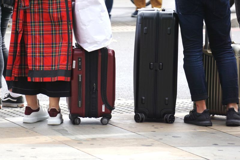 Low section of women with suitcases standing on road