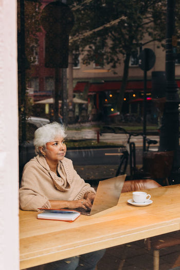 Portrait of woman sitting on table in cafe