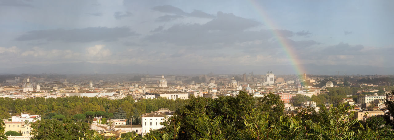 View of rainbow over buildings in city