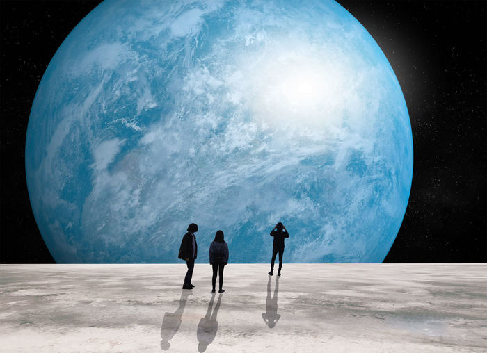 Digital composite image of people standing moon looking at blue planet