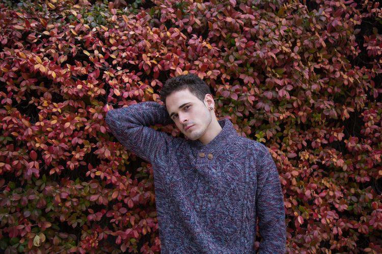Portrait Of Handsome Man Wearing Warm Clothing While Standing Against Plants